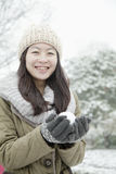 拿着雪球的妇女外面在公园 免版税图库摄影