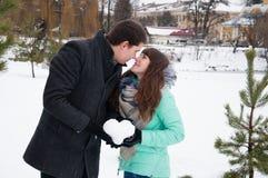 拿着雪的心脏一个爱恋的夫妇人和女孩 免版税库存图片