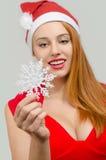 拿着雪花的性感的红色头发妇女 免版税库存图片