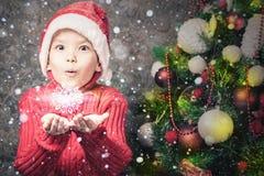 拿着雪花,冬天季节,雪的英俊的被启发的男孩 库存照片
