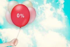 拿着零的百分之气球的手 库存图片