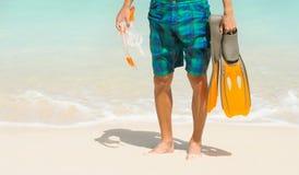 拿着面具和鸭脚板游泳的年轻人 免版税图库摄影