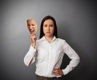 拿着面具的悲哀妇女 免版税库存照片