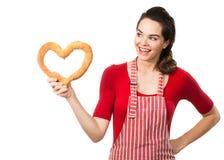 拿着面包爱重点的美丽的妇女。 库存图片