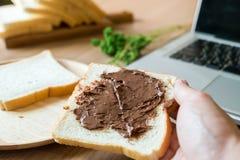 拿着面包用巧克力的一个人被涂,当与膝上型计算机一起使用早晨时 免版税库存照片