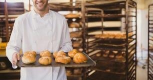 拿着面包的愉快的小企业主人 免版税库存图片