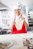 拿着面团的美丽的女性厨师在柜台 免版税库存图片