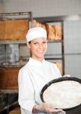 拿着面团盘子的确信的女性贝克在面包店 免版税库存图片