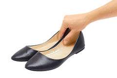 拿着鞋子的妇女的手被隔绝在白色背景 库存图片