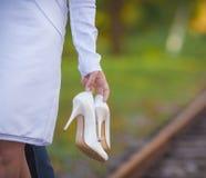 拿着鞋子的新娘 免版税库存照片