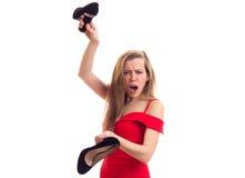 拿着鞋子的红色礼服的少妇 库存照片