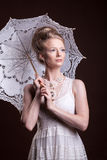 拿着鞋带伞的维多利亚女王时代的样式的美丽的妇女 免版税库存图片