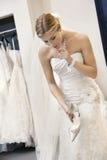 拿着鞋类的婚礼礼服的美丽的迷茫的妇女,当看下来时 免版税库存照片