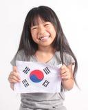 拿着韩国旗子的逗人喜爱的矮小的亚裔女孩画象  免版税图库摄影