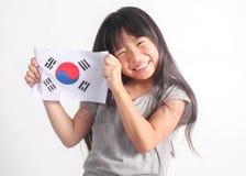 拿着韩国旗子的逗人喜爱的矮小的亚裔女孩画象  免版税库存照片