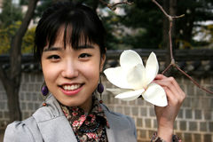 拿着韩文俏丽的妇女的花 库存图片