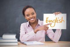 拿着页的愉快的老师显示英语 免版税库存图片