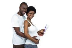 拿着颜色样片的怀孕的夫妇 免版税库存照片