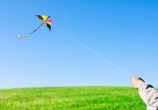 拿着风筝的手反对天空 免版税库存照片