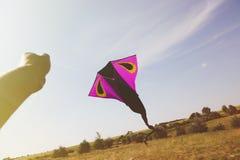 拿着风筝的手反对天空 免版税库存图片
