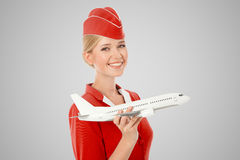 拿着飞机的迷人的空中小姐手中 灰色背景 图库摄影