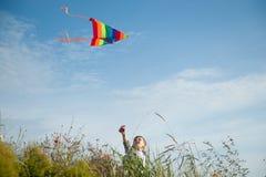 拿着飞行的五颜六色的风筝的滑稽的小男孩站立在领域和天空背景 库存照片