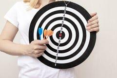 拿着飞镖和箭在手上紧密,瞄准和瞄准在企业和生活概念的妇女 免版税库存照片