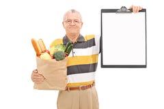 拿着食品杂货袋和剪贴板的成熟人 免版税库存图片