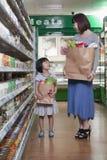 拿着食品杂货袋的母亲和女儿在超级市场,北京 免版税库存图片