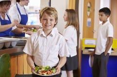 拿着食物的板材白肤金发的头发的男孩在学校食堂 免版税库存图片
