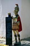 拿着餐馆菜单的一位罗马战士的小雕象 库存图片