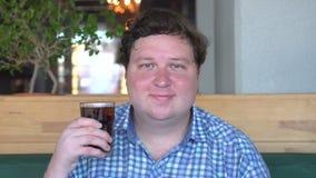 拿着饮料可乐坐在咖啡馆的一杯并且对照相机微笑肥胖人的画象  影视素材