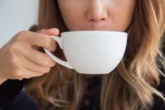 拿着饮用的咖啡杯的特写镜头妇女在cof的早晨 免版税库存照片