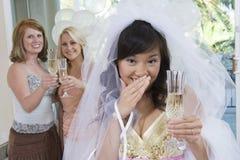 拿着香槟槽的害羞的新娘画象 免版税库存照片