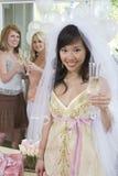 拿着香槟槽的年轻新娘画象 库存图片