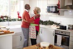 拿着香槟玻璃,笑和拥抱在厨房里的愉快的成熟黑夫妇,当准备在圣诞节morni时的膳食 图库摄影