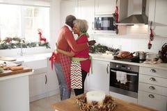 拿着香槟玻璃,笑和拥抱在厨房里的愉快的成熟黑夫妇,当准备在圣诞节morni时的膳食 库存照片