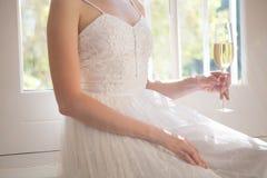 拿着香槟的新娘的中央部位,当坐由窗口时 图库摄影