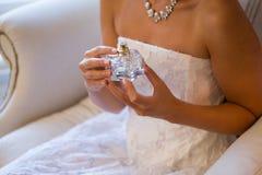 拿着香水喷雾器的新娘的中央部位,当坐扶手椅子时 免版税库存图片