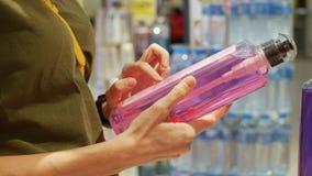 拿着香波或阵雨胶凝体的女性手 妇女读书商品组成在化妆用品商店 消费者至上主义概念 影视素材