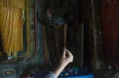 拿着香火的灼烧的棍子手在圣洁佛教寺庙 免版税库存图片