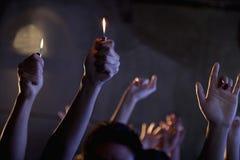 拿着香烟打火机的人在音乐会 免版税库存图片