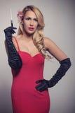 拿着香烟的红色礼服的年轻华美的白种人金发碧眼的女人 库存图片