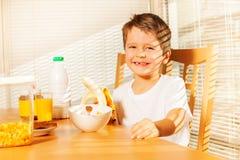 拿着香蕉的微笑的孩子男孩在厨房里 免版税图库摄影