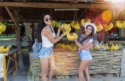 拿着香蕉的美丽的女孩,当购物在新鲜水果少妇愉快的微笑的亚洲义卖市场时街市上  免版税图库摄影