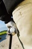 拿着高尔夫俱乐部和球的男性高尔夫球运动员 免版税库存照片