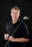 拿着高尔夫俱乐部的年轻人 免版税库存图片