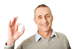 拿着高尔夫球的成熟人 免版税库存图片
