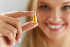 拿着鱼油药片的美丽的妇女手中 健康营养 免版税图库摄影