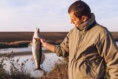 拿着鱼的渔夫 免版税库存照片